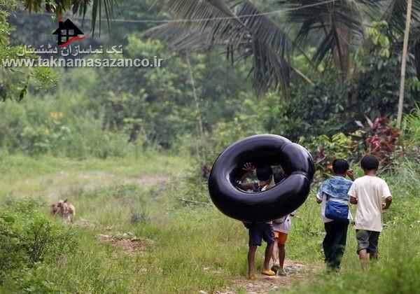 عبور بچه ها از رودخانه با تیوپ برای رفتن به مدرسه در یک روستای دور افتاده در استان ریزال،مانیل،فیلیپین